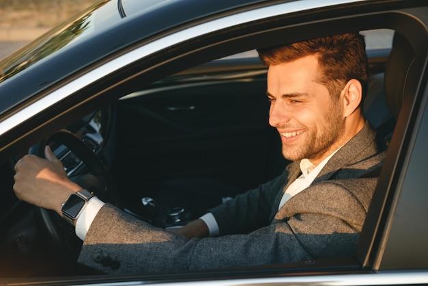 Hombre de negocios feliz en traje de conducción