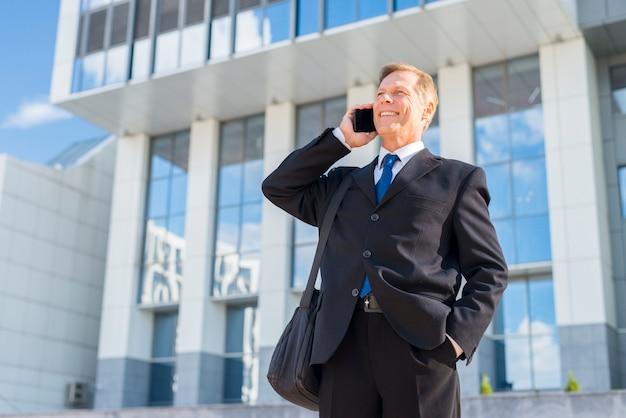 Hombre de negocios feliz usando el teléfono móvil en frente del edificio