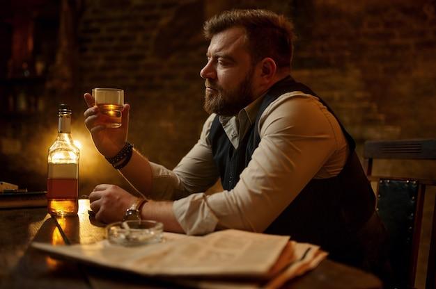 Hombre de negocios fuma cigarrillos y bebe bebidas alcohólicas, interior de oficina vintage. cultura del tabaquismo, sabor específico. fumador masculino