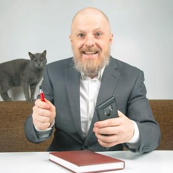Hombre de negocios y gato gris en la oficina en casa trabajando con documentos.