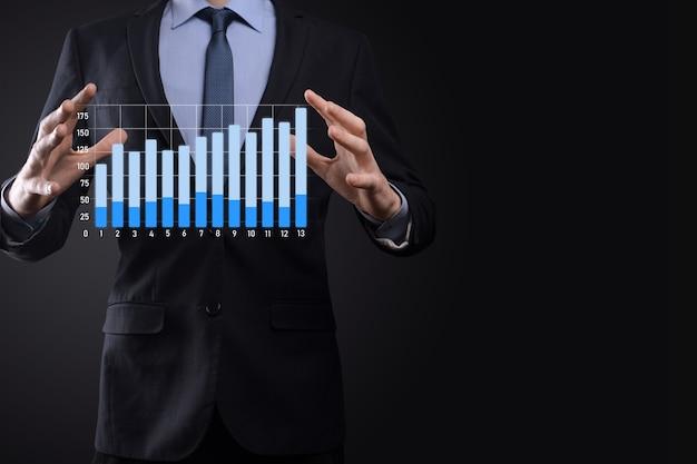 Hombre de negocios con gráficos holográficos y estadísticas del mercado de valores obtienen ganancias