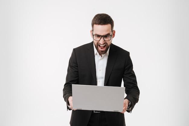 Hombre de negocios gritando con ordenador portátil.