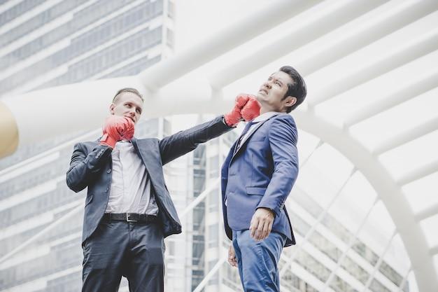 Hombre de negocios con los guantes de boxeo rojos listos para luchar a su compañero de trabajo.