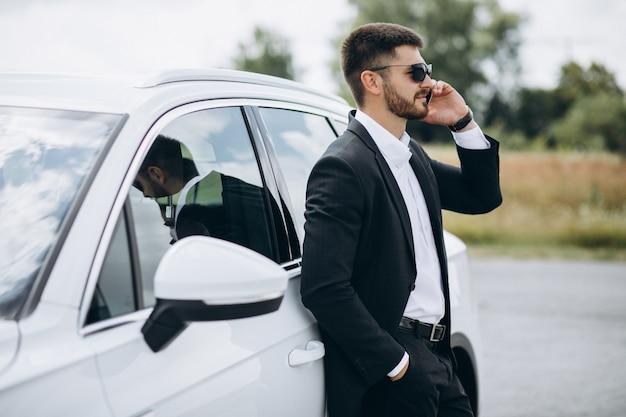 Hombre de negocios guapo en el auto blanco
