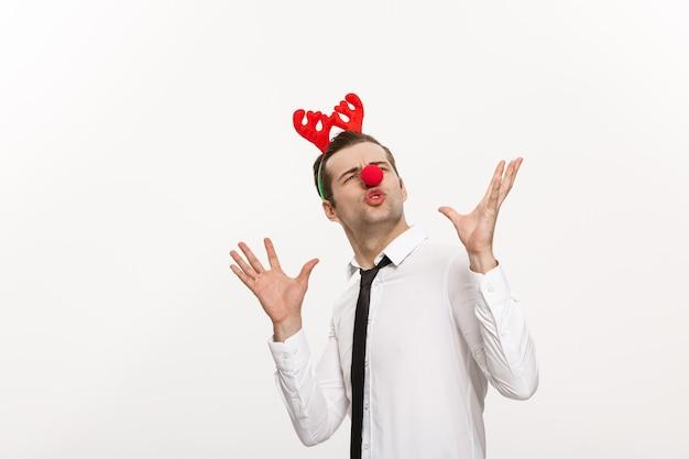 Hombre de negocios guapo con diadema de renos haciendo expresión facial divertida aislado en blanco.