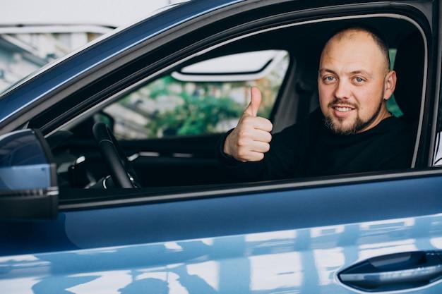 Hombre de negocios guapo eligiendo un coche en una sala de exposición de coches