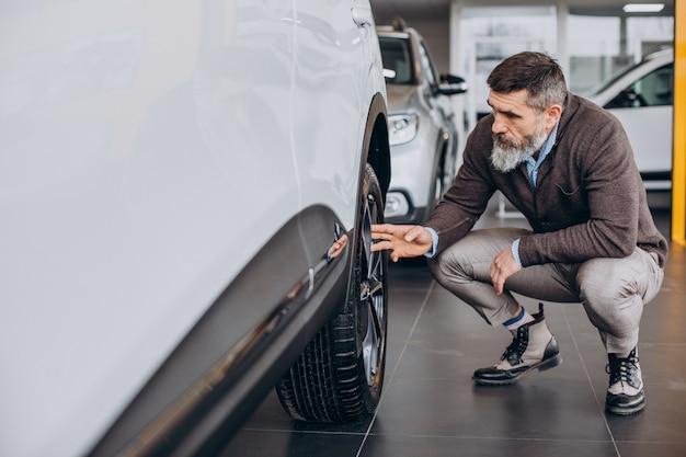 Hombre de negocios guapo eligiendo un coche en la sala de exposición de coches