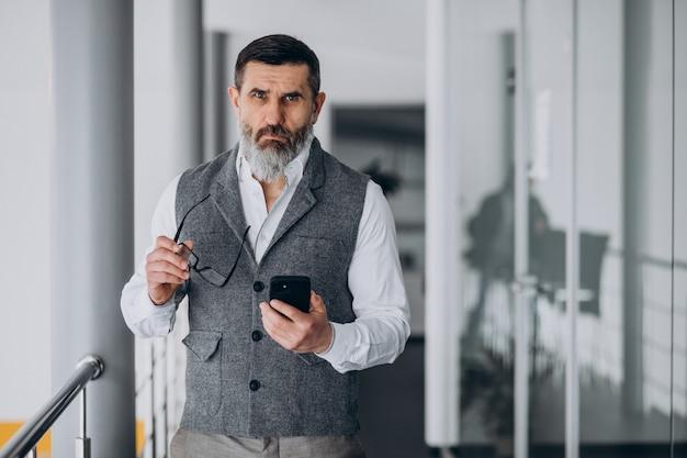 Hombre de negocios guapo hablando por teléfono en la oficina