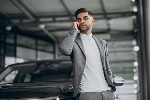 Hombre de negocios guapo hablando por teléfono en una sala de exposición de automóviles