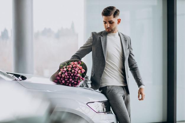 Hombre de negocios guapo joven que entrega ramo de flores hermosas