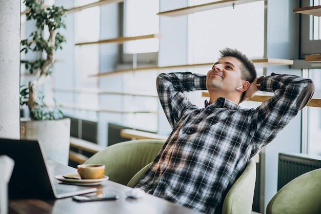 Hombre de negocios guapo joven usando laptop en un café