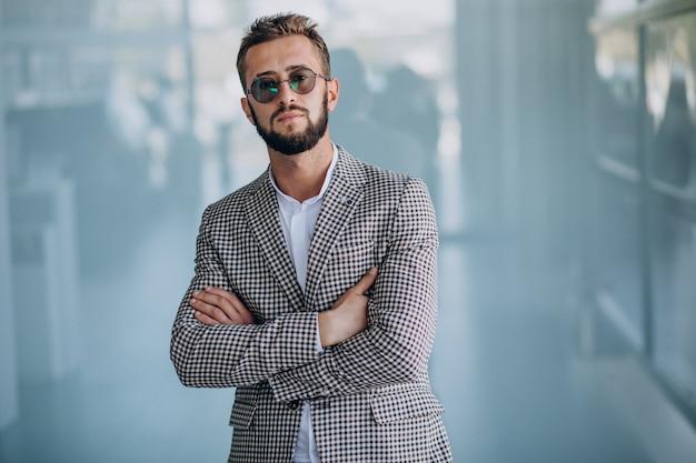 Hombre de negocios guapo de pie en la oficina