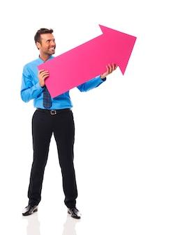 Hombre de negocios guapo sosteniendo una flecha rosa y apuntando al espacio de la copia