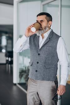 Hombre de negocios guapo tomando café en la oficina