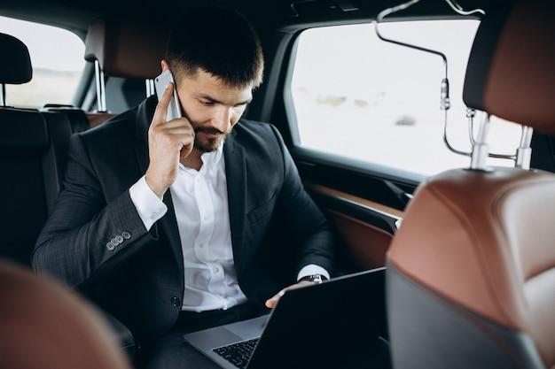 Hombre de negocios guapo trabajando en una computadora en el coche