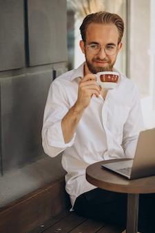 Hombre de negocios guapo trabajando en línea en la computadora de la cafetería