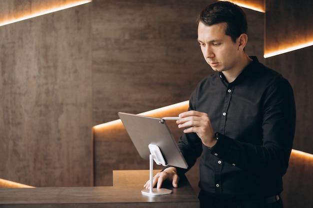 Hombre de negocios guapo trabajando con tableta en oficina
