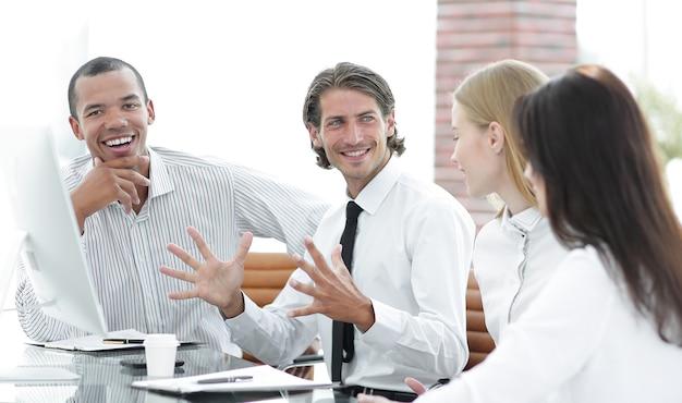 Hombre de negocios hablando con un equipo empresarial sentado en el escritorio