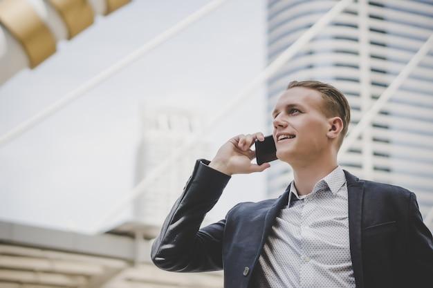 Hombre de negocios hablando por teléfono celular cerca del centro de negocios