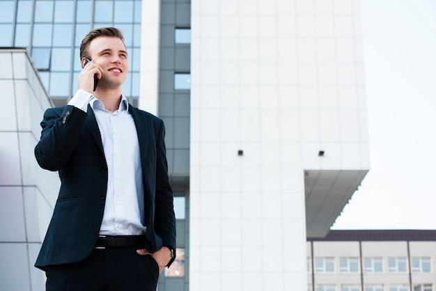 Hombre de negocios hablando por teléfono cerca del edificio