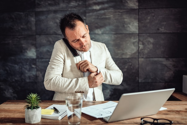Hombre de negocios hablando por teléfono inteligente y haciendo papeleo en su oficina mientras sostiene el brazalete