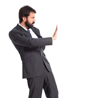 Hombre de negocios haciendo señal de stop sobre fondo blanco