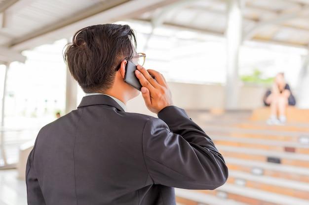 Hombre de negocios hermoso joven de asia con su smartphone que se coloca en la calzada de la ciudad moderna.