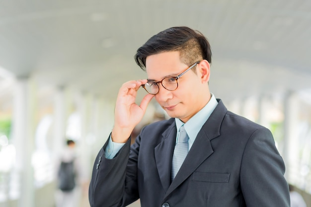 Hombre de negocios hermoso joven de asia con sus vidrios que se colocan en la calzada de la ciudad moderna.