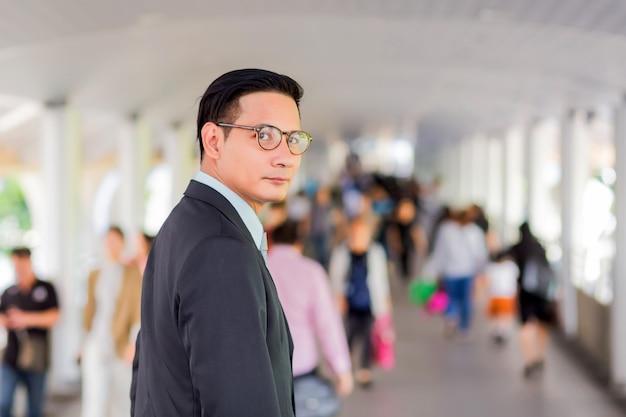 Hombre de negocios hermoso joven de asia con sus vidrios que se colocan en la calzada de la ciudad moderna