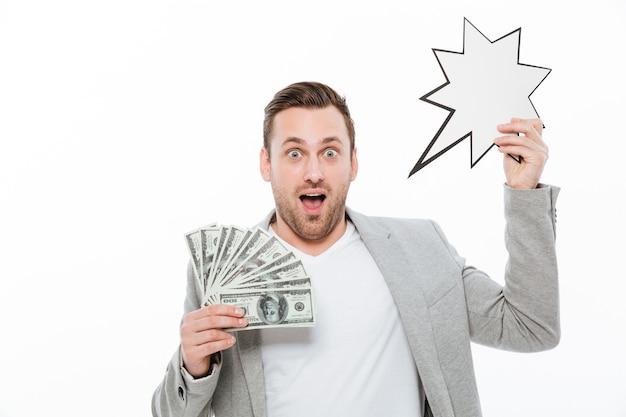 Hombre de negocios hermoso joven emocionado que sostiene el dinero y el bocadillo de diálogo vacío.