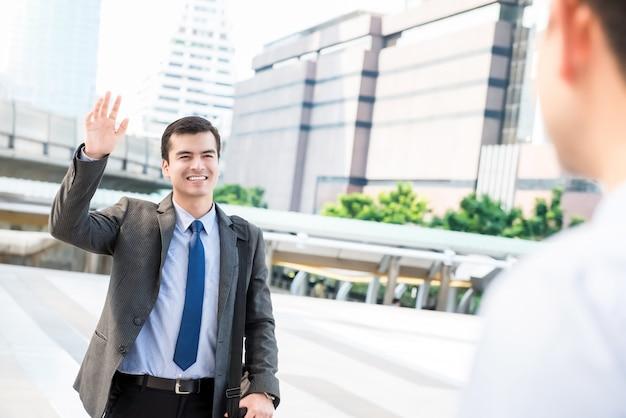 Hombre de negocios hermoso joven que agita la mano a su amigo