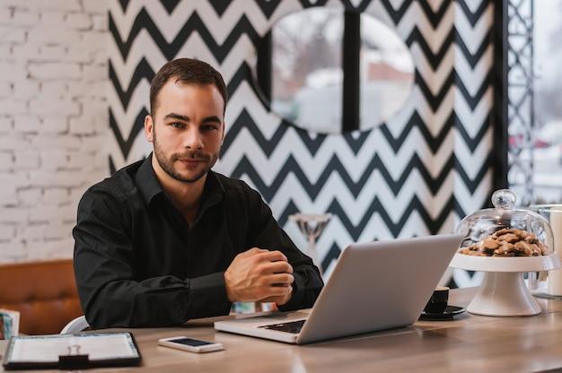 Hombre de negocios hermoso joven que trabaja en el ordenador portátil en café moderno.