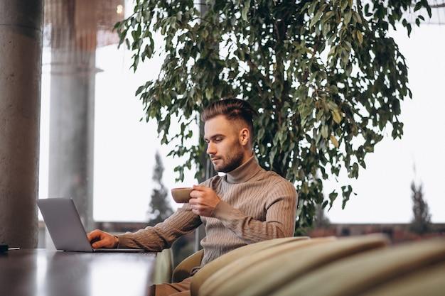 Hombre de negocios hermoso que trabaja en la computadora y que bebe el café en un café