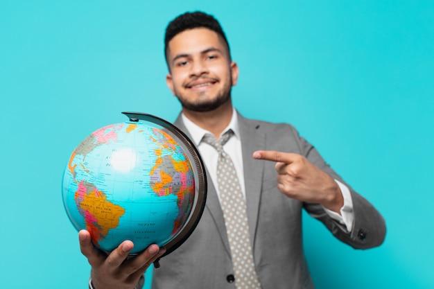 Hombre de negocios hispano apuntando o mostrando y sosteniendo un modelo de planeta mundial
