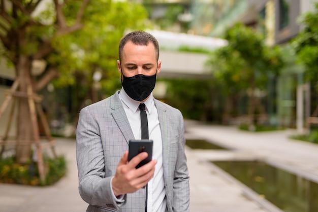 Hombre de negocios hispano calvo con máscara mientras usa el teléfono en la ciudad con la naturaleza al aire libre