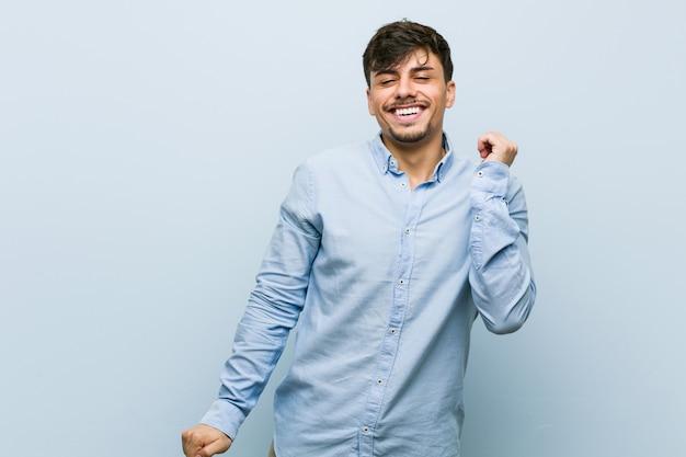 Hombre de negocios hispano joven bailando y divirtiéndose.