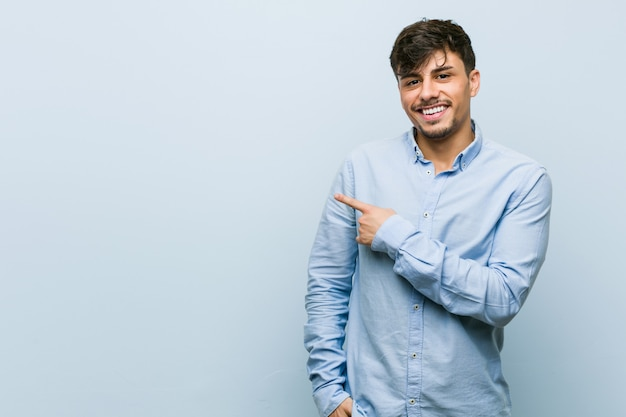 Hombre de negocios hispano joven sonriendo y señalando a un lado, mostrando algo espacio en blanco.