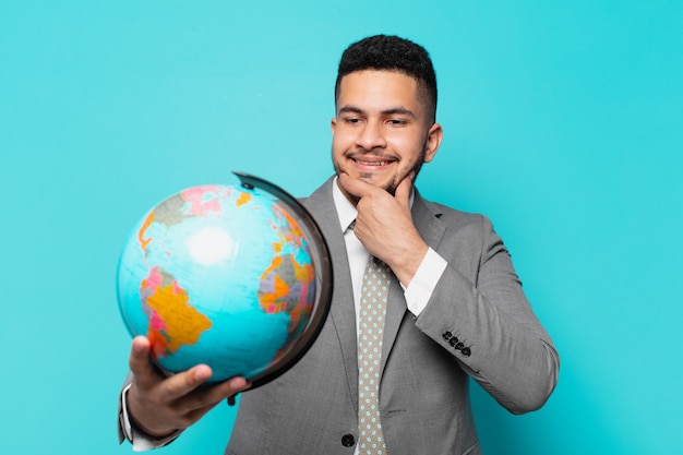 Hombre de negocios hispano pensando en la expresión y sosteniendo un modelo de planeta mundial