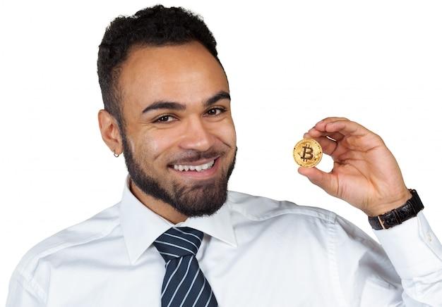 Hombre de negocios del hombre negro que sostiene bitcoin aislado en el fondo blanco