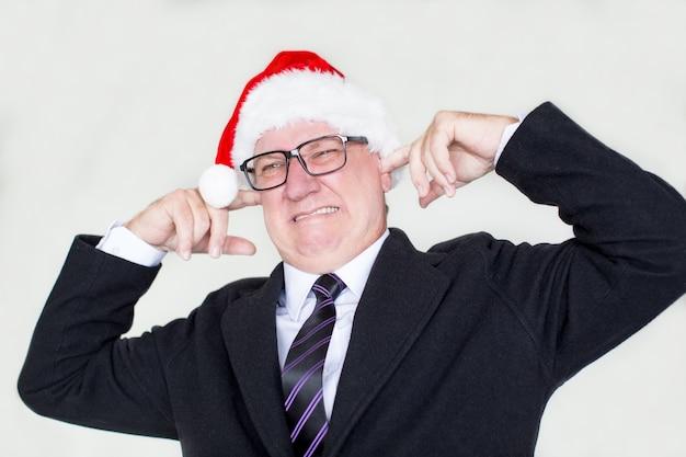 Hombre de negocios hosco en santa sombrero molesto con el ruido