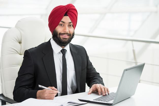 El hombre de negocios indio confiado está trabajando en su computadora.