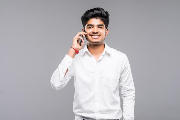 Hombre de negocios indio sonriente que pide smartphone sobre la pared gris
