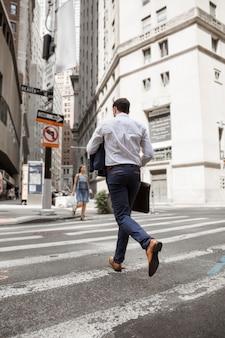 Hombre de negocios irreconocible corriendo en la calle