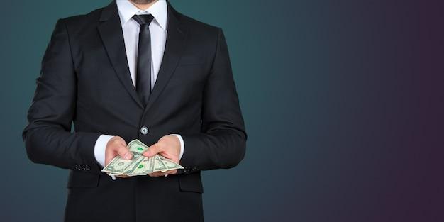 Hombre de negocios irreconocible que le muestra billetes de dólar