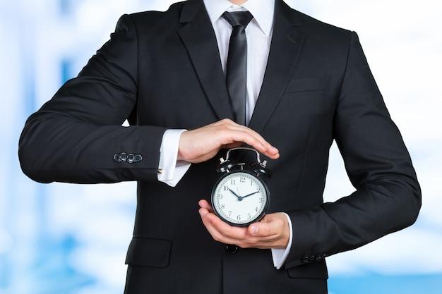 Hombre de negocios irreconocible con un reloj de alarma en una mano