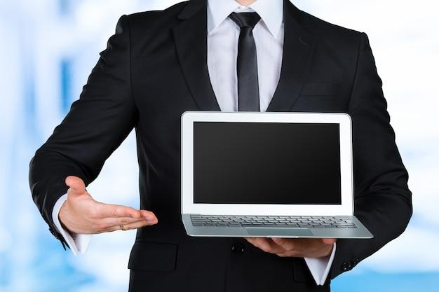 Hombre de negocios irreconocible sosteniendo y mostrando portátil