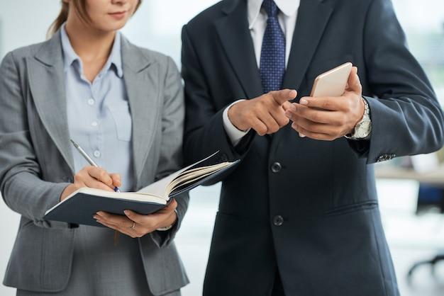 Hombre de negocios irreconocible en traje apuntando al teléfono inteligente en la mano, y una mujer tomando notas