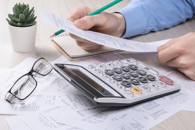 Hombre de negocios irreconocible usando la calculadora en la oficina de escritorio y escribiendo tomar nota con calcular el costo en la oficina en casa.