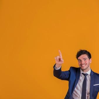 Hombre de negocios joven acertado que señala su dedo hacia arriba contra un contexto anaranjado