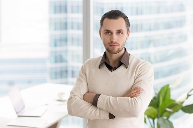 Hombre de negocios joven acertado serio que se coloca en la oficina que mira la cámara
